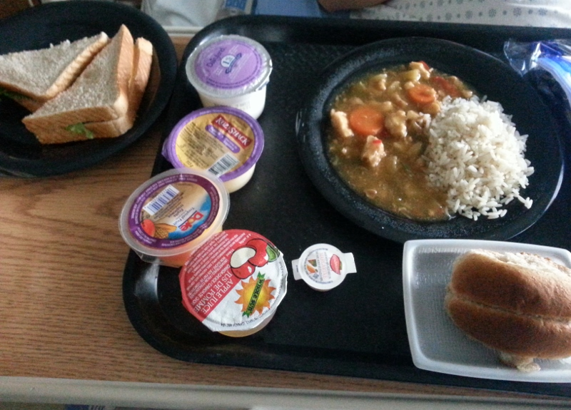 Lunch Deli meat sandwich, beef stew with rice, roll with butter, milk, apple juice, fruit cup and rice pudding